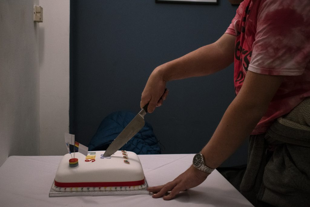 A person cuts SAYiT's 20th Anniversary Cake